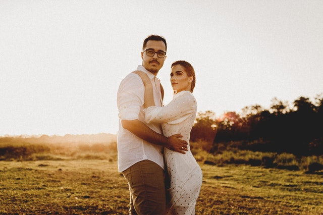Žena v bielych šatách objíma muža v bielej košeli a stoja uprostred lúky počas západu slnka.jpg