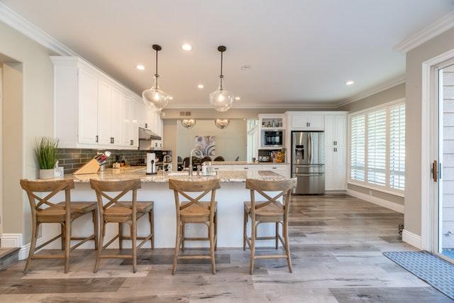 Kuchyňa v bielych farbách s barovými stoličkami a jedálenským pultom.jpg