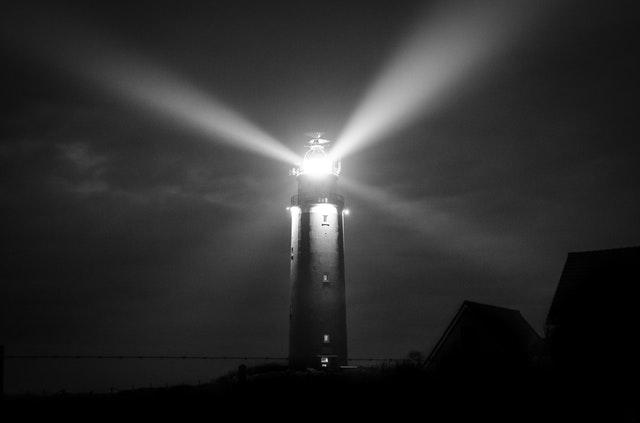 Maják so zapáleným svetlom v tme