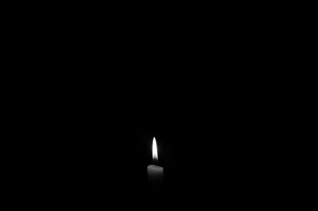 Zapálená sviečka v tme